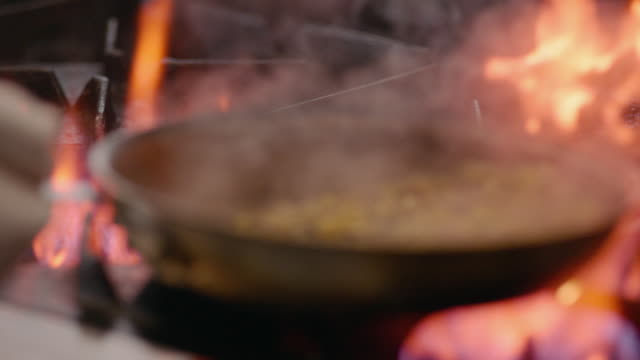 In restaurant kitchen, chef shakes corn succotash in iron skillet over flaming stove in slow motion