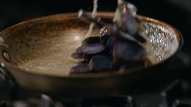 In restaurant kitchen, chef tosses skillet of beets over gas stove in slow motion