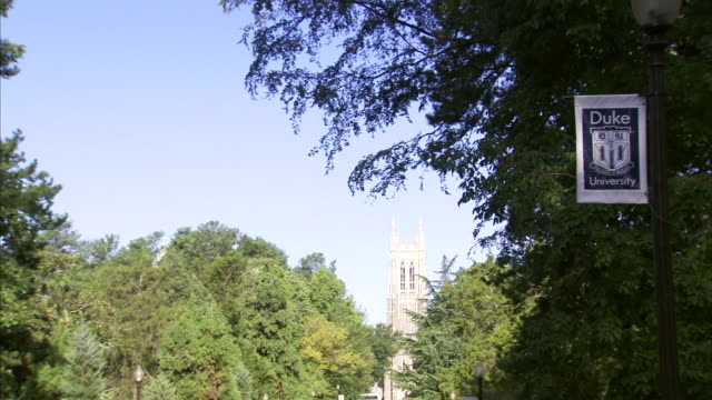 trees duke chapel bell tower in sunny distance duke banner sign hanging on lamp post in front of tree in shaded fg no people - lamp shade stock videos & royalty-free footage