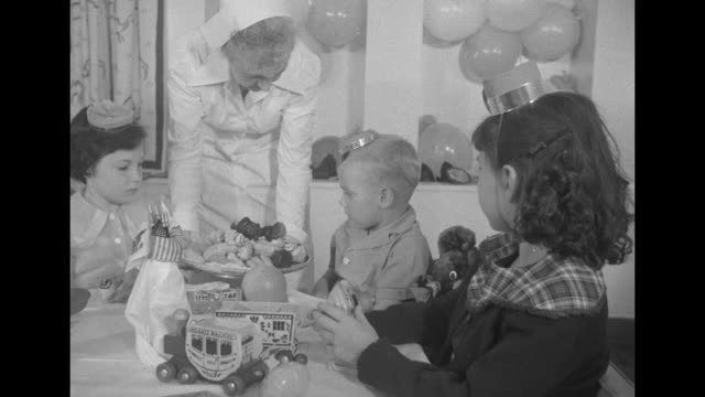 In ship's nursery a nurse in uniform offers bonbons to little girls and a boy in party hats sitting at a small table / older children at another...