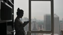 in silhouette asian chinese beautiful woman enjoying her afternoon tea at living room looking outside window relax leaning on table