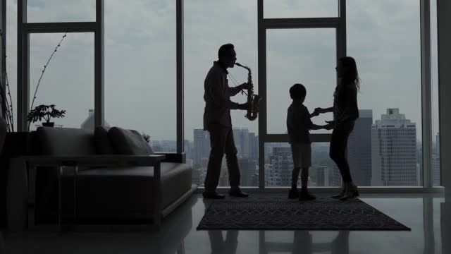 in silhouette asian chinese father enjoy playing saxophone at home with his family during weekend leisure time - atmosphere filter stock videos & royalty-free footage