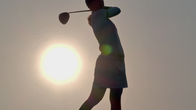 in silhouette of golfer women hit sweeping and keep golf course in the summer for relax time at sunset.female golfer happy for successful putt on the green.women in sport concept. - putting stock videos & royalty-free footage