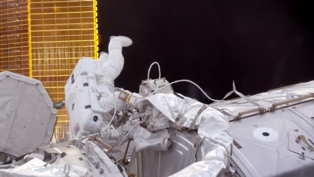 in space: an astronaut working outside the international space station. extravehicular activity in the iss - astronaut stock videos & royalty-free footage