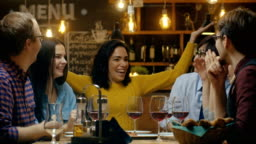 In the Bar/ Restaurant Beautiful Hispanic Woman Shares Good News with Her Dear Friends They Congratulate Her Heartily and Applaud. They Sit in the Stylish Hipster Establishment.