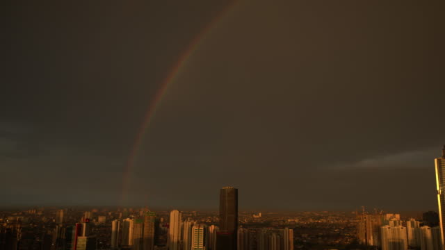 stockvideo's en b-roll-footage met in the cloudy evening sunset sky over the jakarta skyline, a rainbow is formed. below we see an urban cityscape. - home economics