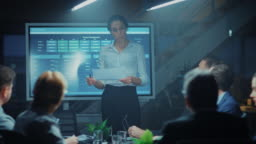 In the Corporate Meeting Room: Female Project Manager Points and Shows Animated Graphs and Statistics on a Digital Interactive Whiteboard, Does talk and Presentation for the Investors, Businesspeople and Executives.
