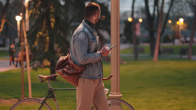 vídeos de stock e filmes b-roll de in the dusk, modern young man, surfing the net on his mobile phone, while push his retro bicycle - cool