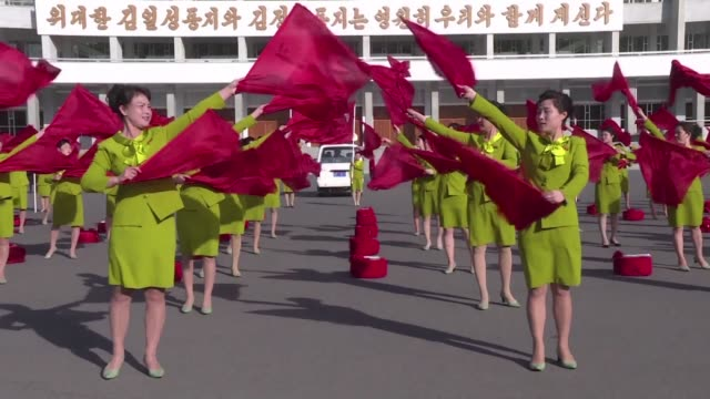 in the early morning in pyongyang women gather to dance with red flags and drums to propaganda music as a way to encourage citizens ahead of a new... - afp stock videos & royalty-free footage