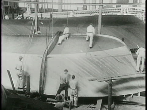 in the elco factory a crew of men building a motorized torpedo 'mosquito' boats for coastal defense / men working on frames waxing the bottom of a... - costruttore navale video stock e b–roll