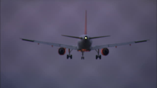 stockvideo's en b-roll-footage met plane lands in the evening on runway with lit lights - landen
