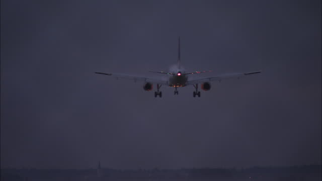 stockvideo's en b-roll-footage met plane lands in the evening - landen