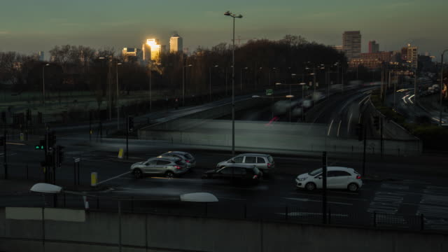 in the far distance early morning sunlight is reflected off skyscrapers at canary wharf in the foreground fast flowing rush hour traffic travels towards central london and moves through a busy local junction - street light stock videos & royalty-free footage