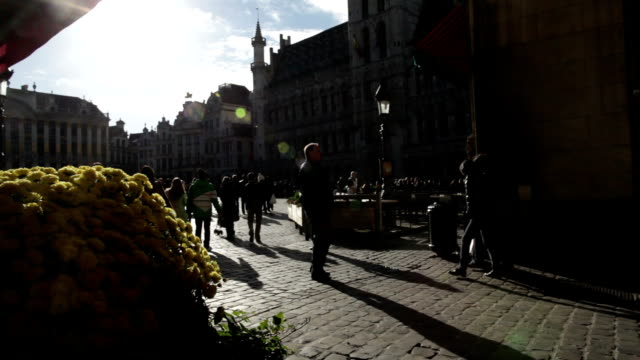 vídeos y material grabado en eventos de stock de in the foreground a large bouquet of yellow chrysanthemums on background tourists enter to the grand place a cool autumn morning in brussels no - crisantemo