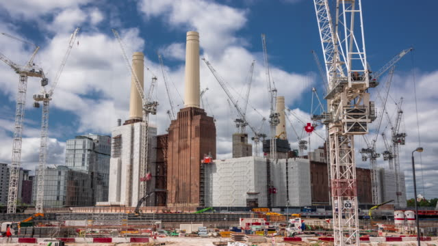 in the foreground local traffic rapidly flows past as over a dozen construction cranes work on the massive redevelopment of the iconic battersea power station - development stock videos & royalty-free footage