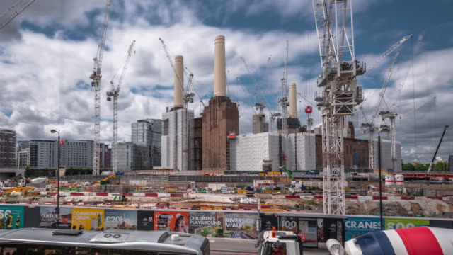 in the foreground local traffic rapidly flows past as over a dozen construction cranes work on the massive redevelopment of the iconic battersea power station - battersea stock videos & royalty-free footage