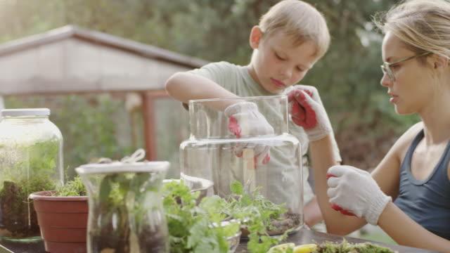 vídeos de stock, filmes e b-roll de diy no jardim. mãe e filho - decoração