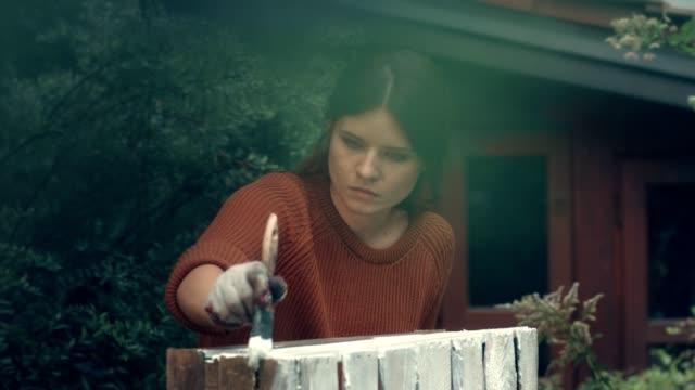 vídeos de stock, filmes e b-roll de diy no jardim. caixa de madeira da pintura de mulher. - feito em casa
