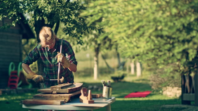 diy in the garden. woman renovating old wooden furniture - protective glove stock videos and b-roll footage