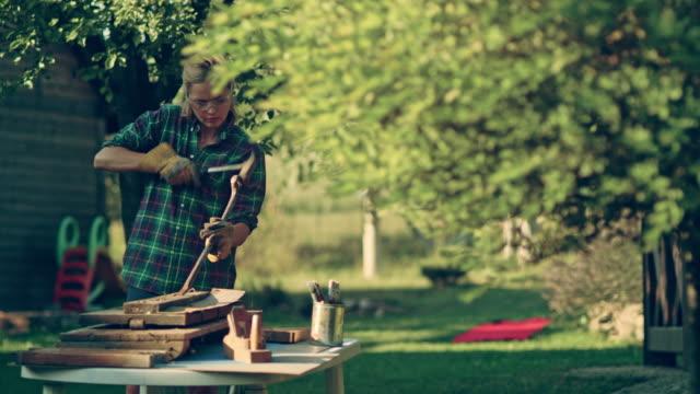 DIY in de tuin. Vrouw renovatie van oude houten meubels