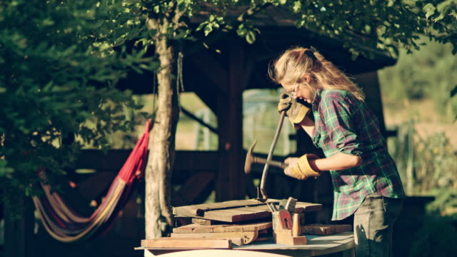 diy in the garden. woman renovating old wooden furniture - hammer stock videos & royalty-free footage
