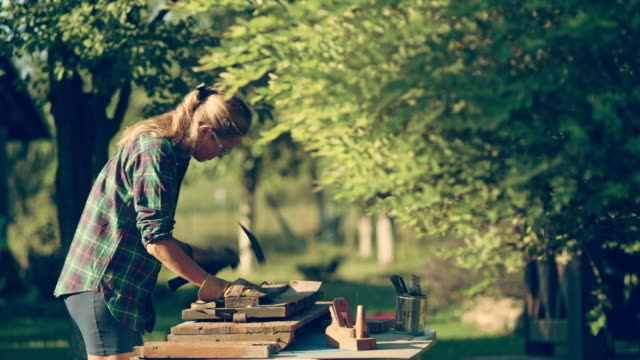 DIY in the garden. Woman renovating old wooden furniture