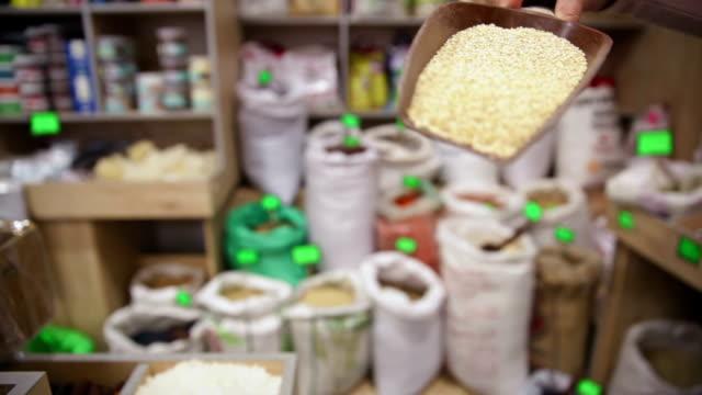 vídeos de stock, filmes e b-roll de a mercearia. tirando trigo groats de saco - brincadeira de pegar