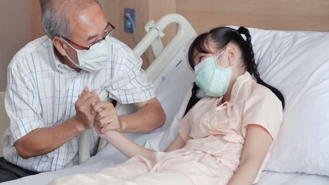 vidéos et rushes de à l'hôpital, le grand-père asiatique heureux ou le père âgé de 56 ans rend visite à sa petite-fille en convalescence de 9 ans qui est couchée sur le lit tout en se tenant la main et en consolant. relation familiale entre grand-parent et petit-enf - new age concept