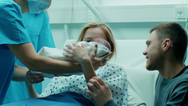 Dans l'hôpital sage-femme donne le nouveau-né d'une mère cale, favorable à père étreindre amoureusement bébé et femme. Héhé dans le quartier moderne de livraison.