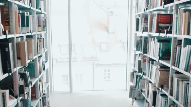 in the library between bookshelves - studentessa di scuola secondaria video stock e b–roll