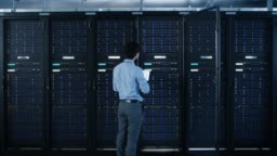 In the Modern Data Center: IT Engineer Standing Beside Open Server Rack Cabinets, Does Wireless Maintenance and Diagnostics Procedure with a Laptop. Zoom Out Camera Shot.