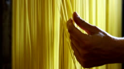 in the morning a young boy touches the hand of a fresh pasta to dry put them to ensure a high quality
