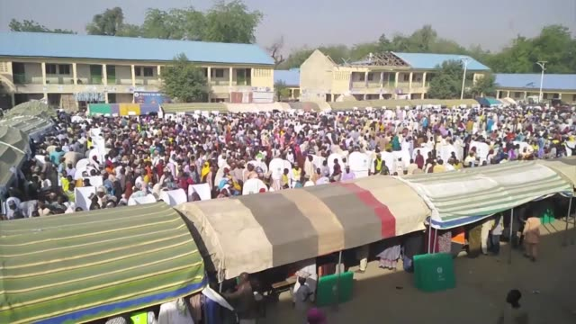 in the northeastern nigerian city of maiduguri dense crowds surround polling booths set up in camps for those made homeless by boko haram - umgeben stock-videos und b-roll-filmmaterial