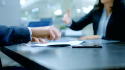 In the Office Close-up on Hands of Businesswoman and Businessman while Signing Contracts and Shaking Hands for Finishing Transaction. Stylish People in Modern Conference Room.