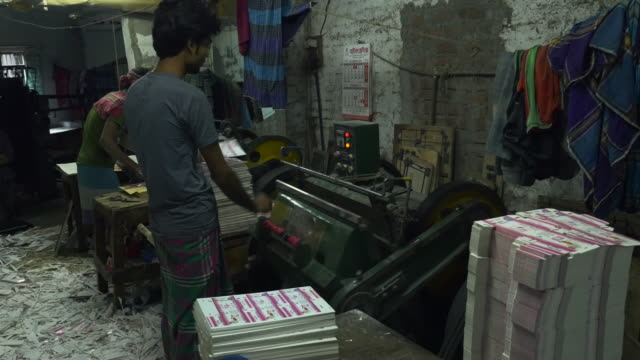 vídeos de stock, filmes e b-roll de in the souks of dhaka bangladesh young men use traditional printing presses and die-cut machines without safety guards - bangladesh