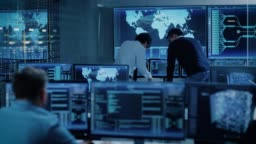 In the System Control Room Project Manager and IT Administrator Have Discussion. Monitoring Station Has Capacity for Global Data and Monitoring, Every Interaction is Shown in Real Time on Displays