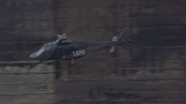 in this aerial daylight shot, an lapd helicopter flies quickly above downtown los angeles buildings. - los angeles police department stock videos & royalty-free footage