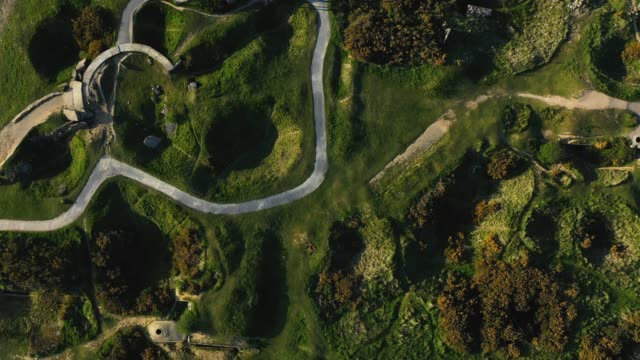 in this aerial view bomb craters lie at la pointe du hoc site of a world war iiera german bunker system and the objective of us rangers during the... - normandie stock-videos und b-roll-filmmaterial