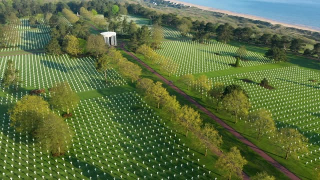 in this aerial view crosses stand over graves at normandy american cemetery on april 30 2019 at collevillesurmer france the cemetery contains the... - normandy stock videos & royalty-free footage