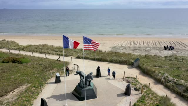 in this aerial view french and us flags fly over a us navy dday memorial at utah beach in normandy on may 2 2019 near saintemariedumont france june 6... - 75th anniversary stock videos & royalty-free footage