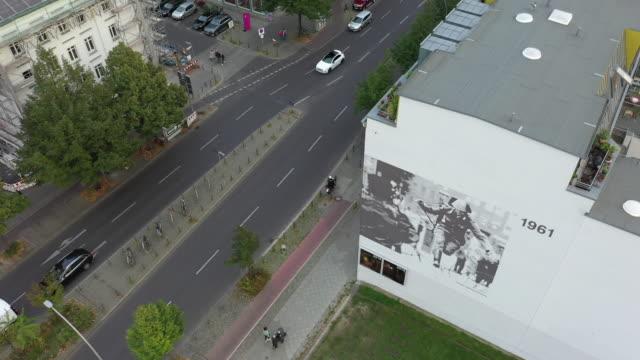 vídeos y material grabado en eventos de stock de in this aerial view from a drone, a large photograph taken 1961 by peter leibing on a house wall remembers the moment, when the former gdr border... - material de construcción