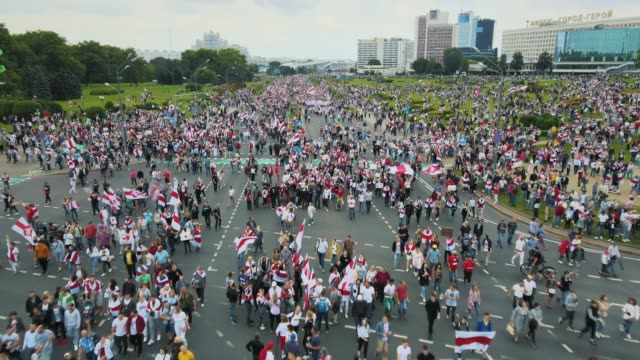 in this aerial view from a drone tens of thousands of people gather in the streets holding the national flag in protest against president alexander... - belarus stock videos & royalty-free footage