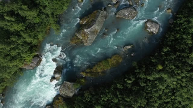 in this aerial view from a drone water from the melting briksdal glacier rushes down a stream in a valley that in the 18th century the glacier still... - ice stock videos & royalty-free footage