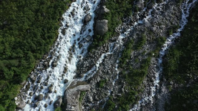 in this aerial view from a drone water runs down a waterfall from the melting tjotabreen glacier on august 11, 2020 near olden, norway. the... - flowing water stock videos & royalty-free footage