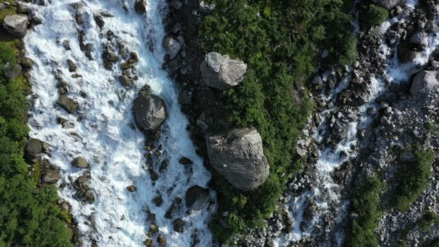 in this aerial view from a drone water runs down from the melting tjotabreen glacier on august 11, 2020 near olden, norway. the tjotabreen glacier is... - flowing stock videos & royalty-free footage