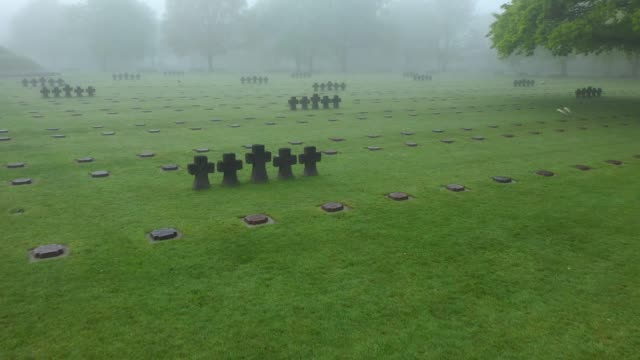 in this aerial view graves lie in morning fog at the la cambe german war cemetery on april 29 2019 near la cambe france the cemetery contains the... - d day stock-videos und b-roll-filmmaterial