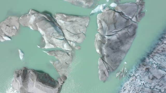 in this aerial view ice lies in a lake formed by meltwater from the rhone glacier on august 19 2019 near obergoms switzerland the covered portion of... - loch stock videos & royalty-free footage