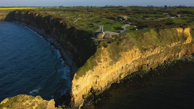 in this aerial view la pointe du hoc site of a world war iiera german bunker system and the objective of us rangers during the dday invasion stands... - normandie stock-videos und b-roll-filmmaterial