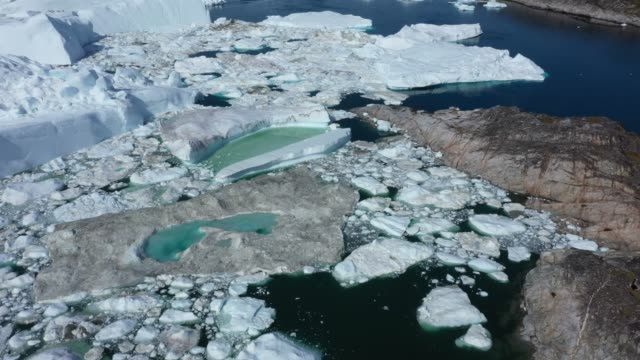 in this aerial view melting ice forms a lake on free-floating ice jammed into the ilulissat icefjord during unseasonably warm weather on july 30,... - greenland stock videos & royalty-free footage