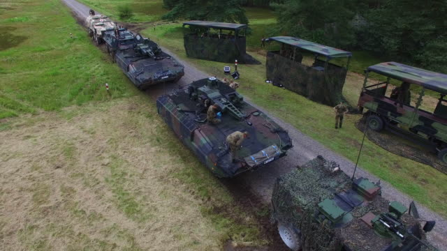 In this aerial view members of the Bundeswehr the German armed forces walk among Puma infantry fighting vehicles and other aromour following a...